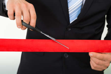 Mittelteil Geschäftsmann schneiden Red Ribbon mit einer Schere auf weißem Hintergrund