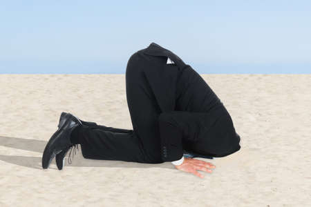 Side view of businessman hiding his head in sand