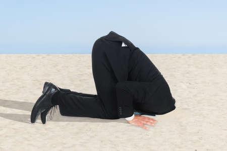 avestruz: Vista lateral del hombre de negocios que oculta su cabeza en la arena