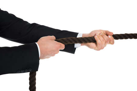 cropped shots: Cropped image of young businessman pulling rope over white background