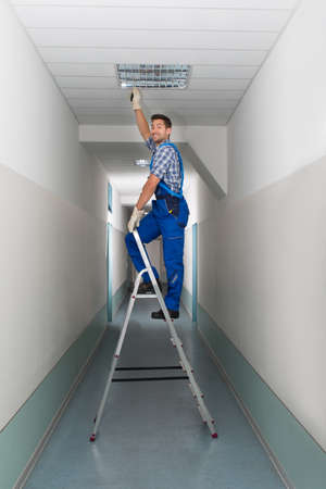 Full length portrait of electrician on stepladder installs lighting to the ceiling in office