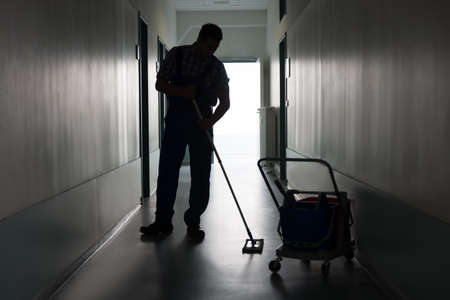 cleaning an office: Full length of silhouette man with broom cleaning office corridor Stock Photo