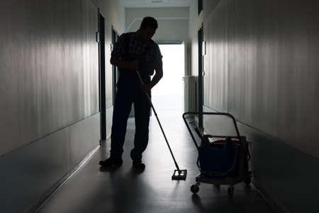 Volledige lengte van silhouet man met bezem schoonmaken kantoor gang Stockfoto