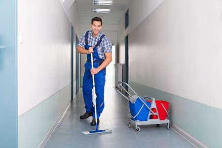 broom: Full length portrait of happy male worker with broom cleaning office corridor
