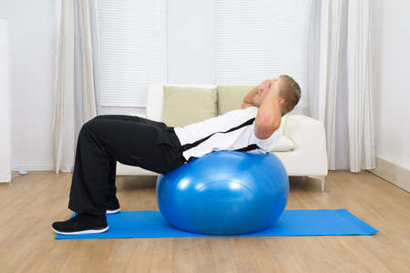 excercise: Healthy Man Doing Abs Exercise On A Blue Pilates Ball