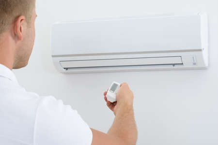 office appliances: Man Operating Air Conditioner With Remote Controller