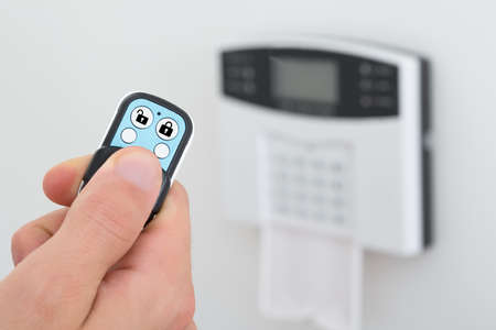 Close-up Of A Person Using Remote Control To Disarm The Security System