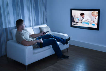 digital television: Portrait Of A Man Watching Television Sitting On Couch Stock Photo