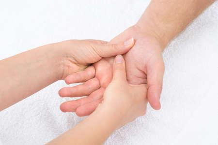 reflexologie plantaire: Close-up d'un physiothérapeute Masser Palm Of A Man Banque d'images