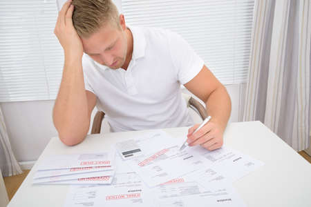 unpaid: Portrait Of A Worried Man Calculating Unpaid Bills Stock Photo