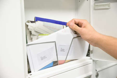 Close-up Of Mans Hand Taking Letter From Opened Mailbox photo