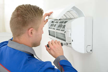cold air: Portrait Of Young Male Technician Repairing Air Conditioner Stock Photo