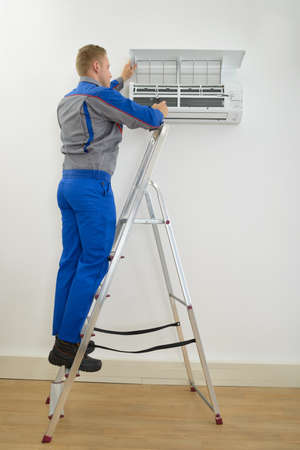Male Technician Repairing Air Conditioner Standing On Stepladder