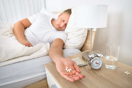 sleeping tablets: Portrait Of Man Holding Pills While Sleeping