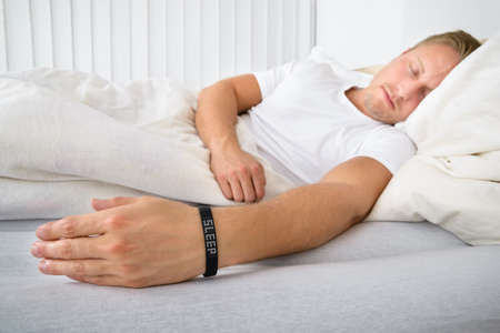 sleeping room: Portrait Of A Man Sleeping On Bed Wearing Smart Wristband
