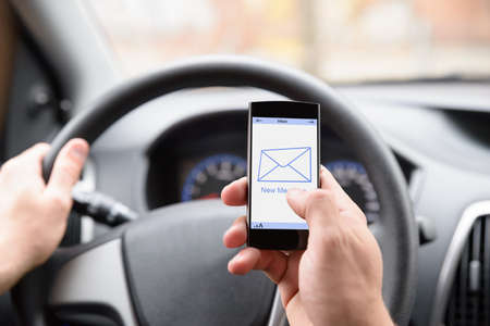 text: Man Holding Cellphone With Message Notification While Driving Car