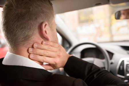 the neck: Vista posteriore di un uomo con dolore al collo durante la guida dell'auto Archivio Fotografico