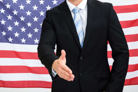 candidates: American Businessman In Front Of Usa Flag Offering Handshake