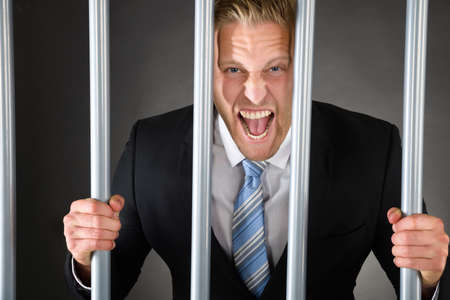 behind bars: Portrait Of Aggressive Businessman Standing Behind Bars Stock Photo