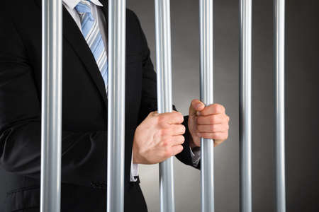 Close-up Of Businessman In Jail Holding Metal Bars