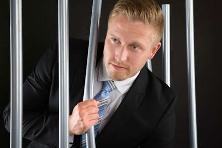 conquered: Portrait Of Young Adult Businessman Escaping From Prison Stock Photo