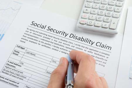 Close-up de la personne à la main avec un stylo et calculatrice remplissage Social Security Disability formulaire de réclamation Banque d'images