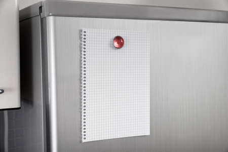 Close-up Of Blank Paper Posted On Modern Refrigerator Door Stock Photo