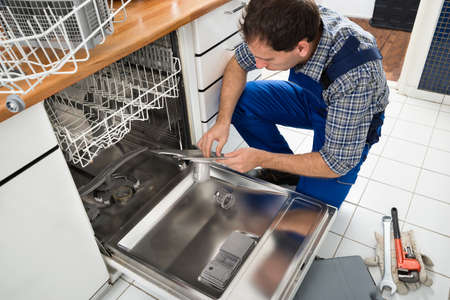 kitchen appliances: Male Technician Sitting Near Dishwasher Writing On Clipboard In Kitchen