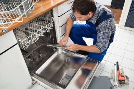 Technicien Homme assis près Lave-vaisselle écriture sur Presse-papiers Dans Cuisine Banque d'images - 35461833