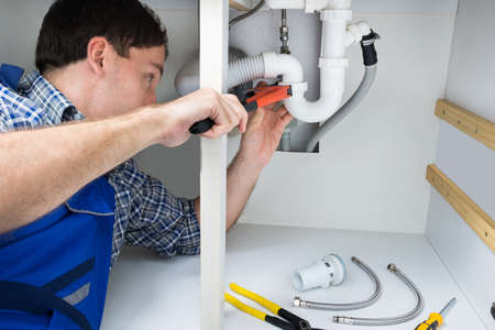 plumber tools: Portrait Of Male Plumber Fixing A Sink In Bathroom