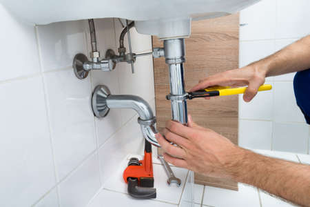 water sanitation: Close-up Of Male Plumber Fixing Sink In Bathroom