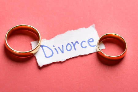 Golden Rings On Torn Piece Of Paper With Divorce Text