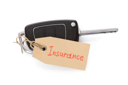 Close-up Of Key Attached With Insurance Tag On White Background photo