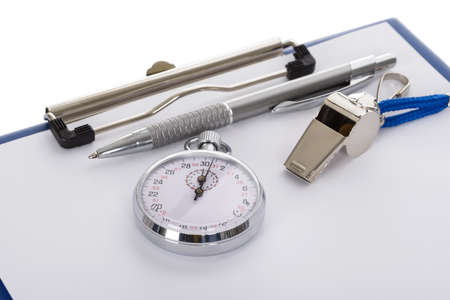 timescale: Close-up Of Clipboard With Whistle; Pen; Paper And Stopwatch On White Background