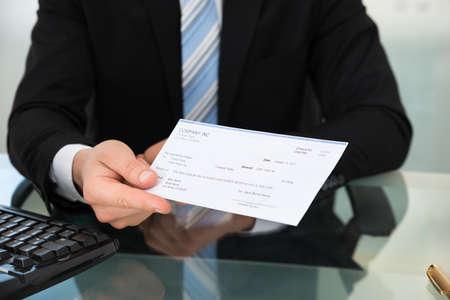 Midsection der Gesch�ftsmann zeigt Pr�fung am Schreibtisch im B�ro