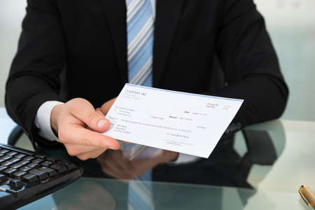 cheque: Midsection of businessman showing cheque at desk in office