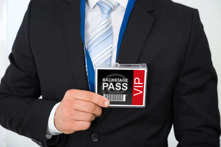 Midsection of businessman with backstage pass in office