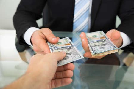 Recorta la imagen de hombre de negocios que pasa el dinero a su colega en la mesa