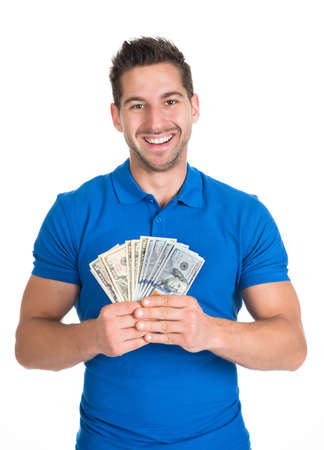 us paper currency: Portrait of smiling young man holding fanned US paper currency isolated over white background