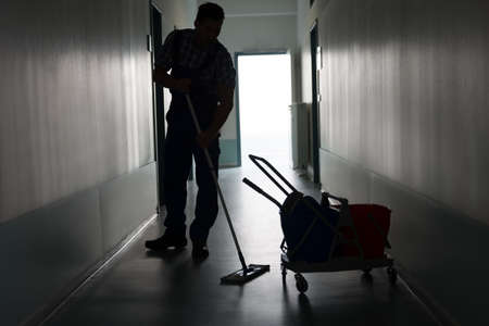 service: Full length of silhouette man with broom cleaning office corridor Stock Photo