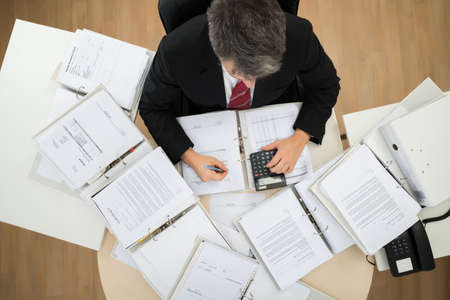 High Angle View Of Businessman Calculating Invoices At Office Desk