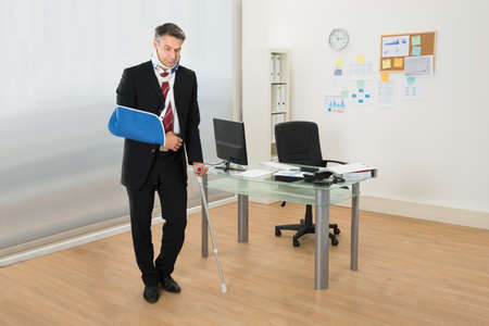 crutch: Portrait Of Disabled Businessman Standing With Crutches In Office Stock Photo