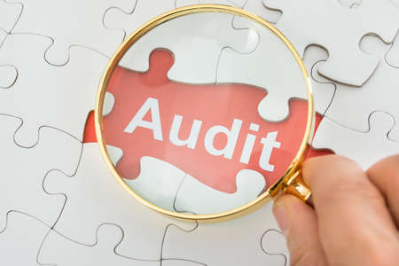 Close-up Of Persons Hand Holding Magnifying Glass Over Audit Text photo