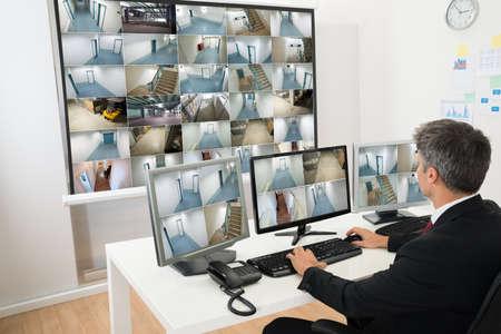 sicurezza sul lavoro: Man In Control Room Monitoring multipla Cctv Footage