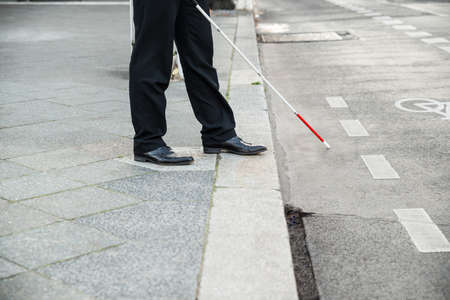 people with disabilities: Low Section Of A Blind Person Crossing Street