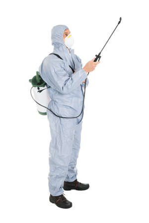 protective workwear: Pest Control Worker In Protective Workwear And Mask Spraying Pesticides Over White Background
