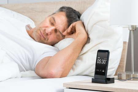 Homem maduro que dorme na cama com alarme em uma tela do telefone celular digital