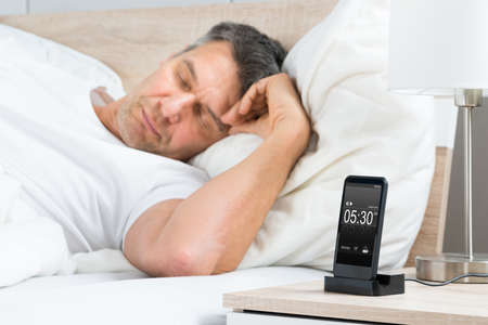 early morning: Mature Man Sleeping On Bed With Alarm On A Digital Cell Phone Display