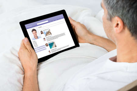 Close-up Of Man Chatting On Social Networking Sites Using Digital Tablet Stock Photo