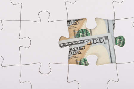 hidden taxes: Close-up Of White Jigsaw Puzzle Over American Banknote Stock Photo